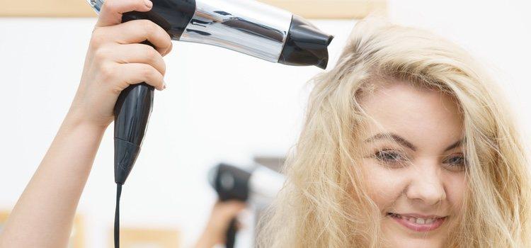 Mujer pelirroja con secador de pelo