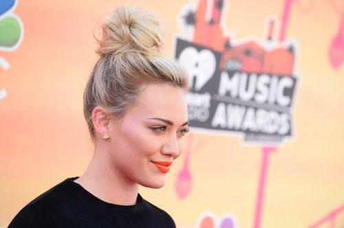 Hilary Duff con un moño alto y labios naranjas