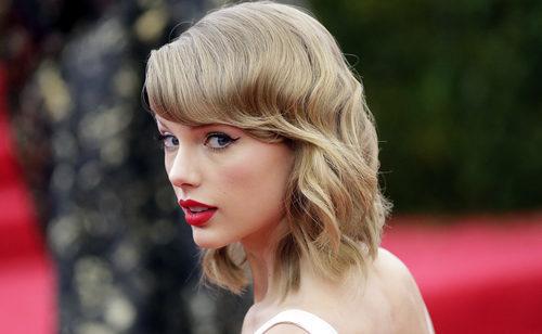 Taylor Swift con flequillo desfilado y pelo ondulado