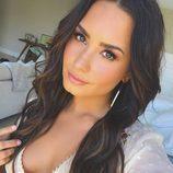 Demi Lovato con extensiones y maquillaje en tonos melocotón