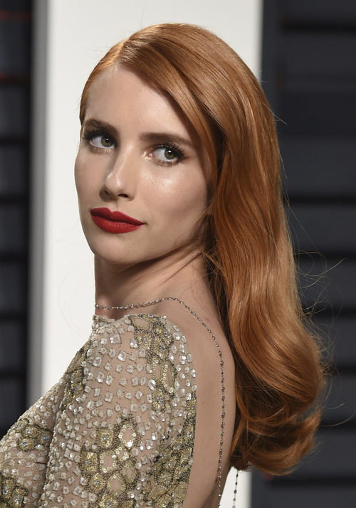 Emma Roberts con melena pelirroja y peinado clásico