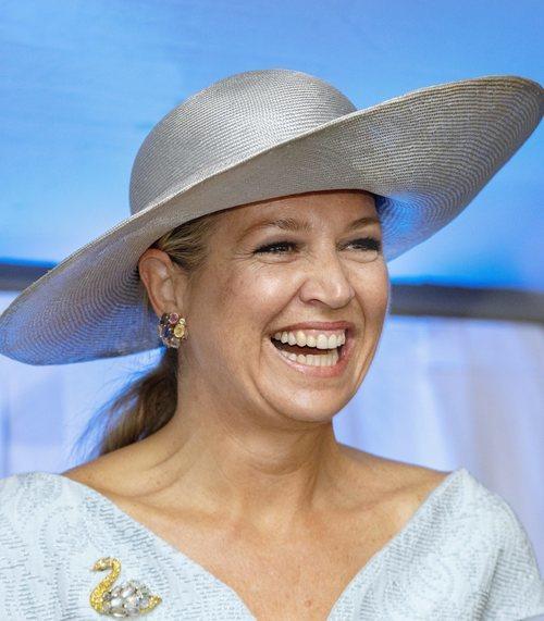 Reina Máxima de Holanda con pamela de rafia plateada y vestido azul en la inauguración de un centro de equinoterapia