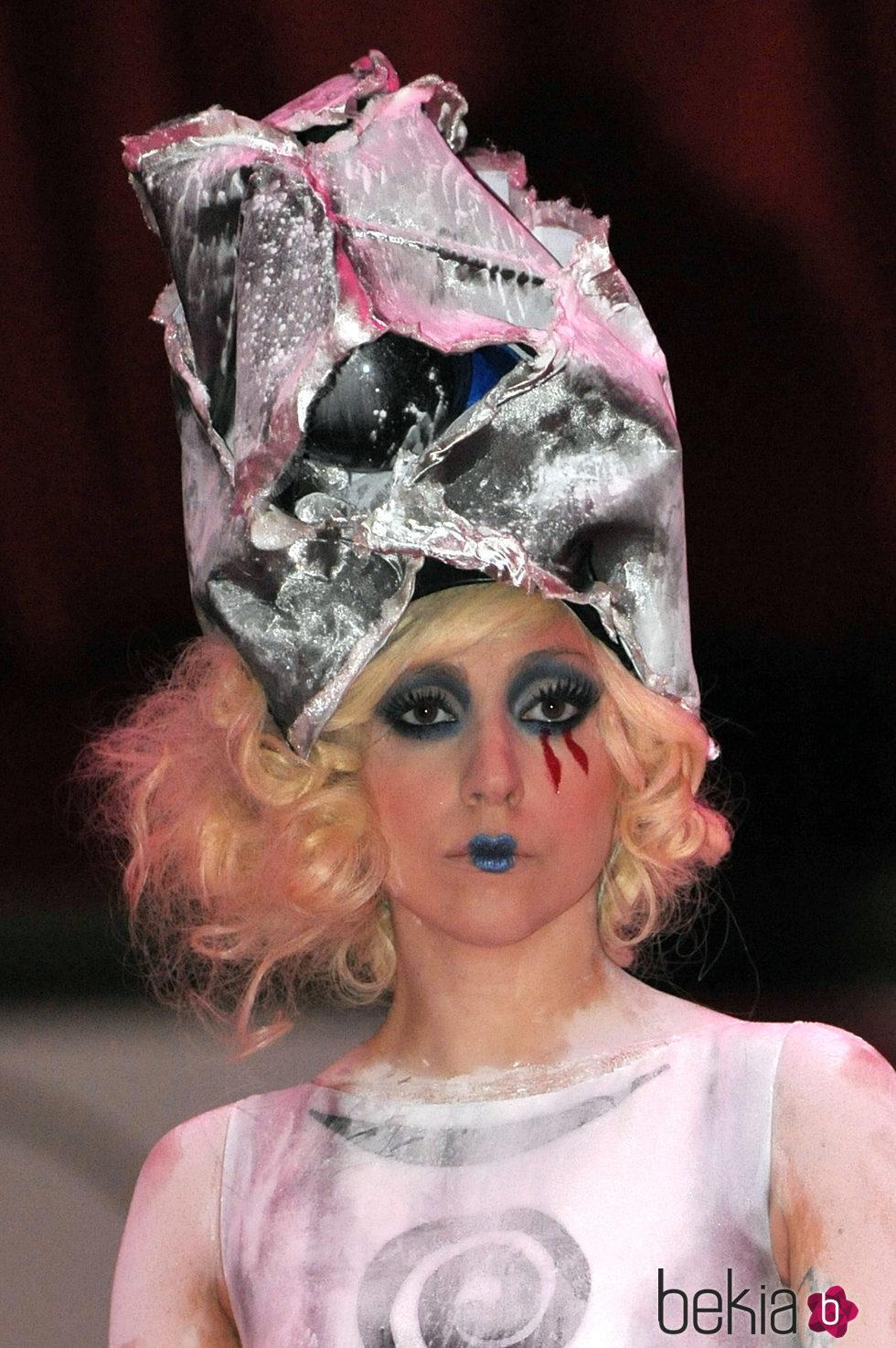 Lady Gaga con sombrero rosa metalizado y lagrimas de sangre