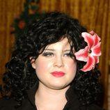 Kelly Osbourne con melena ondulada negra y tocado de flor